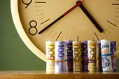 An analog clock and rolls of paper money