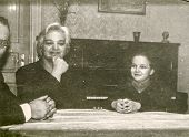 Vintage photo of parents sitting at the table with little girl, fifties