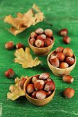 Hazelnuts in wooden bowls on wooden background