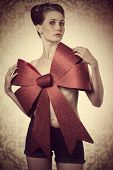 stock photo of adornment  - lovely blonde woman adorned like a sensual christmas present with big red bow on her naked breast - JPG