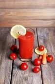 Glass of tomato juice with lemon and fresh tomatoes on wooden table on wooden wall background