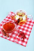 Goji berries drink in glass cup and cinnamon, fruit drink in glass teapot on red checkered napkin on light blue wooden background