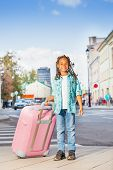 African smiling girl holding pink luggage in city