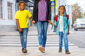 stock photo of pedestrian crossing  - Smiling African kids with woman safely walking over the crossing on the street holding grown - JPG