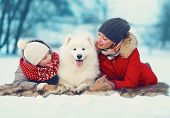 Beautiful Happy Family, Mother And Son Walking With White Samoyed Dog In Park On A Winter Day