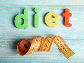 Diet word formed with colorful letters on wooden background