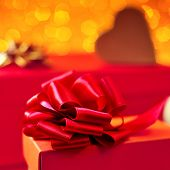 closeup of a red gift box with a red ribbon and some gifts in the background