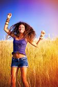smiling happy young woman jumping in sunny grass field