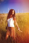 smiling beautiful woman with long curly hair in romantic dress stand in grass field