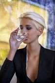young blond woman drinking water in cafe