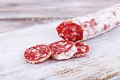 French salami on cutting board on wooden background