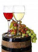 Wine in goblets and grapes on barrel isolated on white