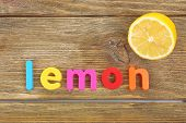 Lemon word formed with colorful letters on wooden background