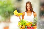Shopping concept. Beautiful young woman with fruits and vegetables in shopping basket on shop background