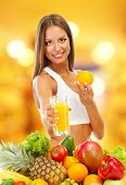 Shopping concept. Beautiful young woman with fruits and vegetables and glass of juice on shop background