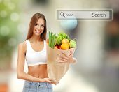 Shopping concept. Beautiful young woman with vegetables and fruits in shopping bag on shop background