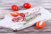 French salami with tomatoes on cutting board on wooden background