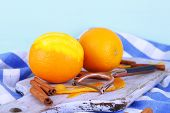 Oranges on cutting board on napkin on blue background
