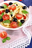 Spaghetti with tomatoes, olives and basil leaves on plate on pink lace napkin on wooden background