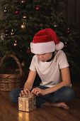 Boy in Santa hat with  Christmas gift.