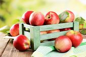 Sweet apples in wooden box on table on bright background