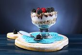 Healthy breakfast - yogurt with  fresh berries and muesli served in glass bowl, on dark color background