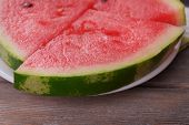 Slices of watermelon on plate on wooden table