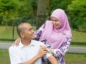 Southeast Asian Muslim couple at outdoor park, happy family lifestyle.