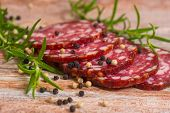 foto of grease  - salami slices with pepper and rosemary on wooden background - JPG