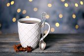 Cup of tasty hot tea, on wooden table, on shiny background