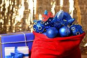 Red bag with Christmas toys and gifts on fabric background