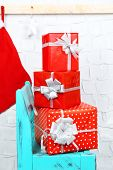 Christmas presents on blue chair on brick wall background