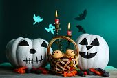 White Halloween pumpkins, candies and candles on wooden table on dark color background