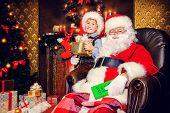 Santa Claus and laughing cute boy sitting in Christmas room with gifts. Christmas home