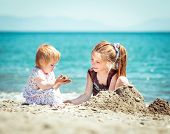 happy little girl and her sister  sitting on the beach builds a tower of sand