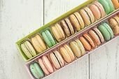 box with macaroons on wooden background