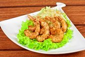 Fried shrimps with lettuce at white plate