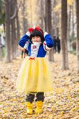 little girl dress in snow white costume in forest during halloween