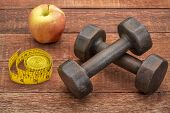 dumbbells, apple and tape measure against weathered barn wood - a fitness concept