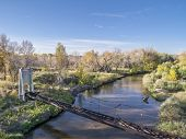 aerial view of Cache la Poudre River and old irrigation aqueduct, fall scenery shot from low flying drone