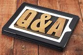 questions and answers - Q&A in vintage letterpress wood type on a digital tablet against red barn wood