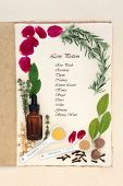 Pagan love potion ingredients over natural hemp notebook and mottled cream paper background. With ingredient list.