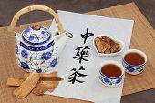 Astragalus herb tea also used in chinese herbal medicine, with cups and calligraphy script on rice paper over bamboo. Translation reads as chinese herbal tea.