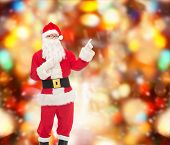 christmas, holidays, gesture and people concept - man in costume of santa claus pointing fingers over red lights background