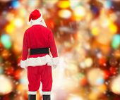 christmas, holidays and people concept - man in costume of santa claus from back over red lights background