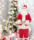 christmas, holidays and people concept - man in costume of santa claus over tree lights background