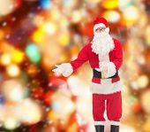 christmas, holidays, gesture and people concept - man in costume of santa claus over red lights background