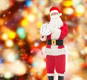 christmas, holidays and people concept - man in costume of santa claus with clock showing twelve pointing finger over red lights background