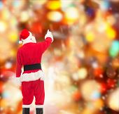 christmas, holidays and people concept - man in costume of santa claus pointing finger from back over red lights background