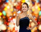 shopping, wealth, holidays and people concept  - smiling woman in evening dress holding credit card over red lights background